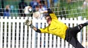 A goal keeper goes vertical to stop a shot on goal during a soccer match