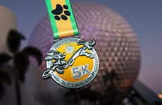 Walt Disney World 5K medal in front of Spaceship Earth at Epcot during Walt Disney World Marathon Weekend.