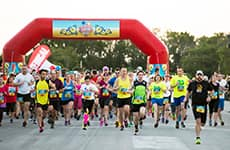 Runners cross the start line of Disney Cruise Line's Castaway Cay 5K for the Disney Castaway Cay Challenge.