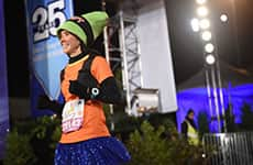 Runner dressed as Goofy finishes race during Walt Disney World Marathon Weekend.