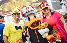 Runners with Donald Duck at the Walt Disney World Half Marathon finish line.
