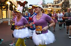 Runners dressed as Daisy run through Magic Kingdom during Walt Disney World Half Marathon.