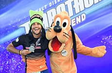 Runner celebrates with Pluto after the Walt Disney World 5K.
