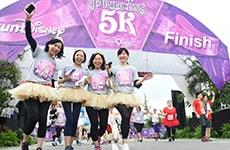 Group of girlfriends run through the finish line of the Disney Princess 5K at Walt Disney World Resort.