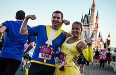 Runners dressed as Belle and Beast pose in front of Cinderella Castle during Disney Princess Half Marathon at Walt Disney World Resort.