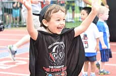 Kid runner celebrates after running the runDisney Kids Races during Star Wars Half Marathon – The Dark Side race weekend