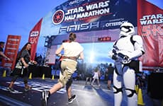 Runner races through the finish line during Star Wars Rival Run Weekend.