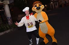 Runner dressed as Chef Louis with Timon during the Disney Wine & Dine Half Marathon