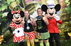Runners celebrating with Mickey Mouse and Minnie Mouse after the Disney Wine & Dine Half Marathon