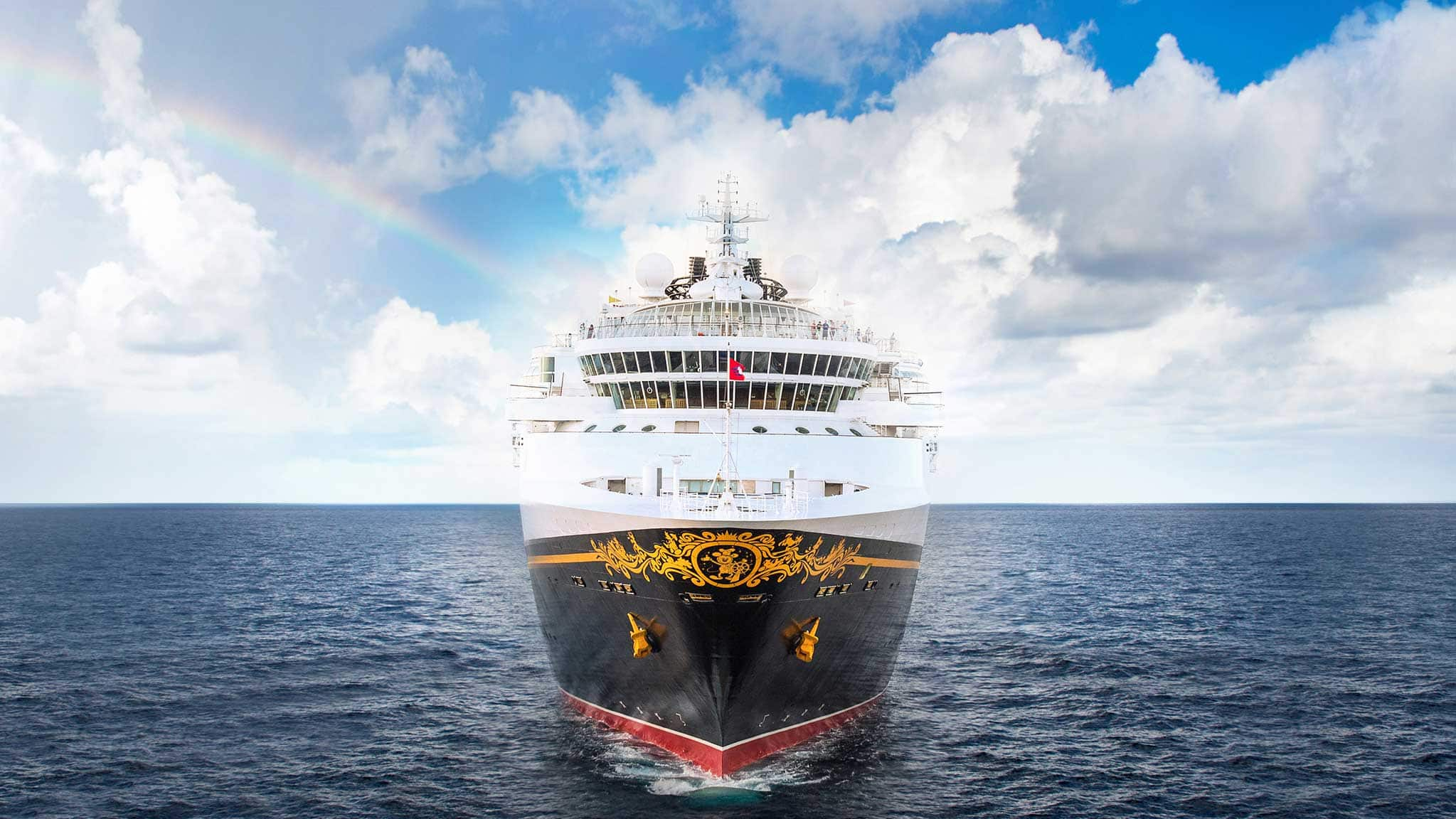 A Disney Cruise Ship Cuts Through The Ocean With Clouds And Rainbow In Sky