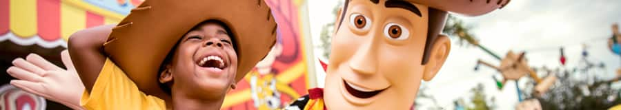 A smiling young boy dressed in a Woody costume T shirt and hat stands beside Woody at Toy Story Land