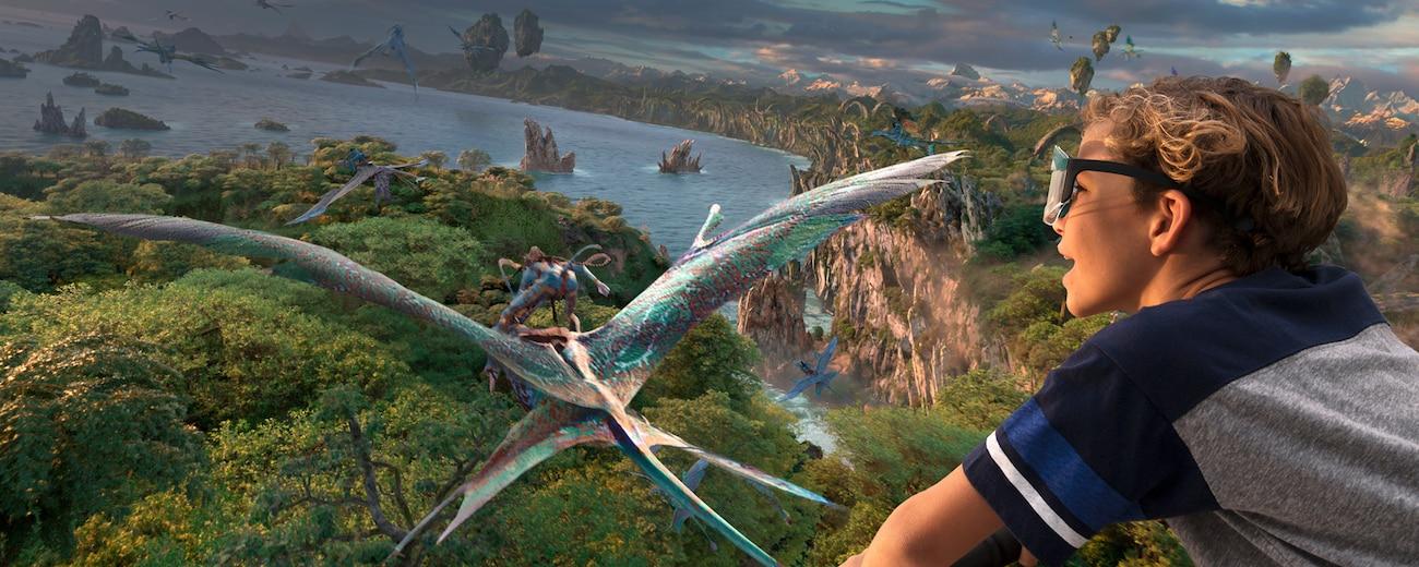 A boy flies through the sky with Na'vi and Mountain Banshees through the skies over Pandora