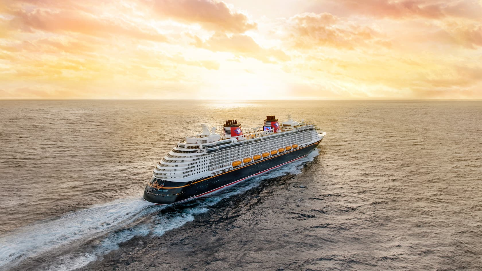 The Disney Dream crusie ship glides across the sea as the sun sets