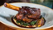 A lamb shank served atop sautéed spinach and parsnip puree