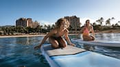 Two women kneeling on paddle boards, head out on the calm water of Ko Olina Lagoon at Aulani Resort