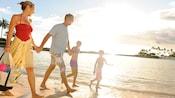 Un hombre y una mujer con su hijo e hija caminan por una playa tropical.