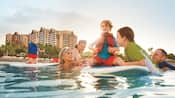 At Aulani Resort, parents swim near their 3 children on a surfboard and a fourth who paddles on hers