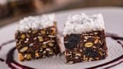 2 cubes comprised of chocolate, seeds and nuts topped with shredded coconut