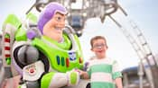 A young boy is all smiles meeting Buzz Lightyear at Tomorrowland