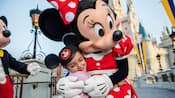 A young child wearing a Mickey ears hat hugs Minnie Mouse near Cinderella Castle