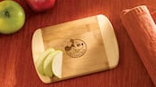 Apple slices on a Walt Disney World Passholder cutting board, which features Mickey Mouse in a chefs hat