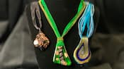 3 necklaces featuring murano glass on decorative ribbons