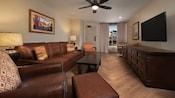 Una habitación con un sofá, 4 sillas, una otomana, una mesa, 2 lámparas, una TV y una mesa ratona