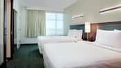 A hotel suite bedroom with 2 queen sized beds.