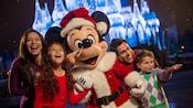 Cuatro miembros de una familia rodean a Mickey vestido de Santa Claus, frente al Cinderella Castle iluminado durante las fiestas