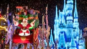 Santa Claus rides inside an ornate sleigh in front of Cinderella Castle