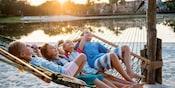 Cuatro niños se relajan en una hamaca cerca de un lago