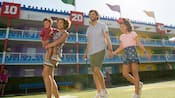 A family of four stroll through the courtyard at Disney's All Star Sports Resort