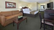 Mini suite with a desk, queen bed, nightstands, lamps, table, chairs, sofa,  art, console, phone and TV