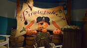 A display for Piratepalooza with a pirate-themed banner, barrels, treasure and jack o lanterns