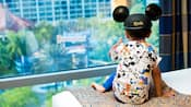 A young boy wearing a Mickey Mouse ear hat sits on a bed inside his hotel room while glancing out the window and pointing at the Disneyland Hotel pool area