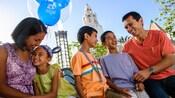 Una familia sonriente de cinco integrantes pasea en Disney California Adventure Park con un globo de Mickey