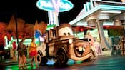 A family stands next to Mater from the Cars films, with a diner in the background
