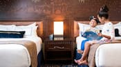 Two children read a book while sitting side by side on a bed inside of their hotel room