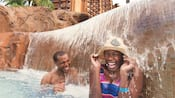 A man and a woman in a hat, laugh while under a waterfall in a pool at Aulani Resort