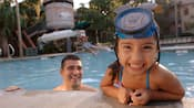 A little girl with a Mickey snorkle mask leans on the side of the pool while her dad watches