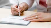 Close-up of a woman's hands writing in a checkbook