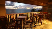 High tables and chairs on the patio overlook the ocean below