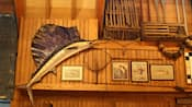 A wood-paneled wall with a stuffed swordfish, fish pictures, a net and fishing boat gear