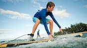 A boy attempts to stand on a surfboard in low surf