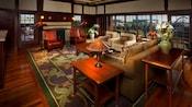 Una sala abierta con sofá, 2 sillones, 2 sillas de cuero y una pared de ventanas
