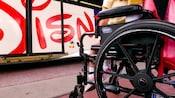 Un joven Visitante está sentado pacientemente en una silla de ruedas mientras espera para subirse a un autobús de Walt Disney World Resort