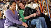 Two female Guests accompanied by a canine service animal while riding Prince Charming Regal Carousel
