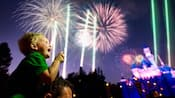 A child sits on his father's shoulders and looks in wonder at the fantastic Disneyland fireworks
