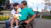 A man in a wheelchair holds his son on his lap; his son holds a Donald plush toy