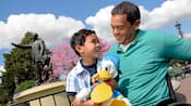 A man in a wheelchair holds his son on his lap and rolls past the Partners Statue in Disneyland Park
